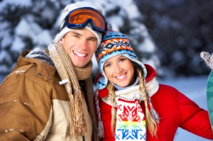 Skiing couple smile happily, showing off the dental veneers they got in Jefferson City from Dr. Justin Johnson.