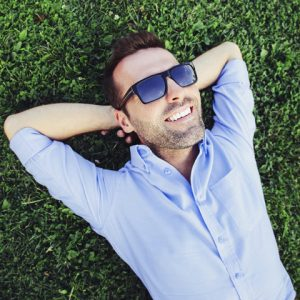 Man lies on the grass after this laughing gas sedation dentistry appointment in Jefferson City.